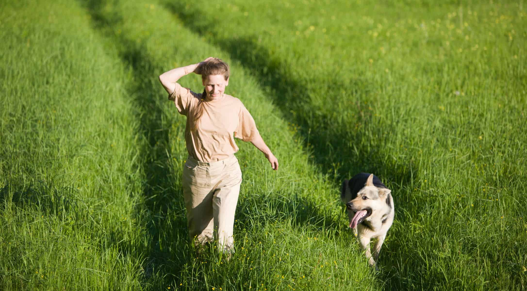 Woman and dog in deep grass